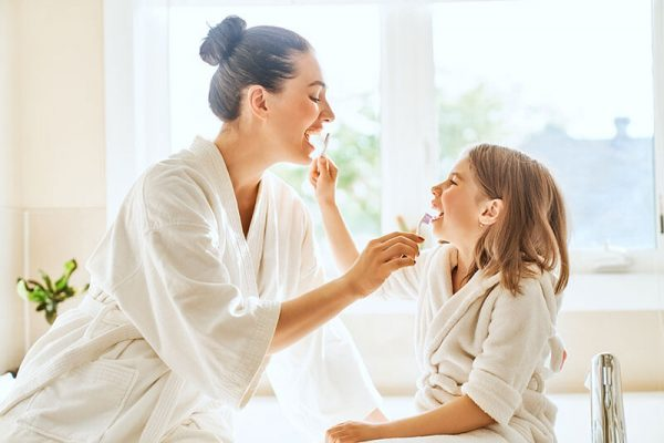 Mom and young daughter brushing each other's teeth