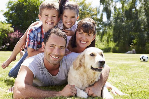 Happy family of four and their dog outdoors
