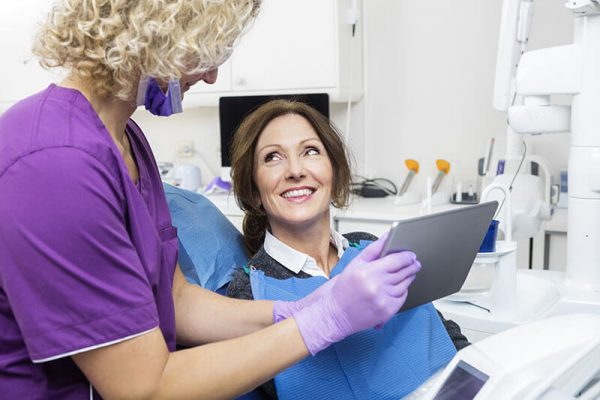 Middle-aged female patient smiling at a hygienist