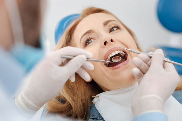 Middle-aged female patient getting her teeth examined
